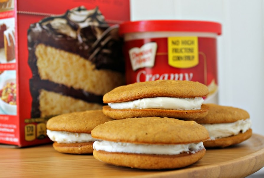 These Pumpkin Whoopie Pies start with a doctored up cake mix and then are filled with cream cheese frosting. Fast AND delicious!