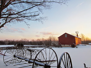 Photo: Sunset on snow and a red barn behind old farm machinery at Carriage Hill Metropark in Dayton, Ohio.