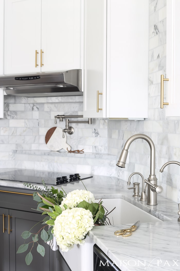 traditional kitchen with grey and white cabinets, brass cabinet pulls and contrasting chrome sink faucet