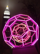 Photo: Buckyball by Leo Villareal- Madison Square Park Art. New York City  This is a large-scale work by light installation artist Leo Villareal called Buckyball that is on display in Madison Square Park until February 1, 2013.  The work's two nested geodesic spheres are comprised of 180 LED-tubes arranged in a series of pentagons and hexagons that contain thousands of individual pixels capable of displaying 16 million distinct colors. Controlled by custom software designed by the artist, the 30 foot tall illuminated sculpture animates Madison Square Park's natural landscape with dynamic, random light sequences of varied color, opacity, speed, and scale.  Zero-gravity couches, are placed at the base of the sculpture to allow viewers to gather and contemplate the artwork. The couches and sculptural aspects of the installation reference elements of the park and add a physical and temporal dimension to the viewer's multisensory experience of Buckyball.  —  I went for a little walk in the fog last night and ended up sitting on one of the zero-gravity couches in Madison Square Park (as mentioned above) and staring at this installation for quite a long time since it constantly changes. This installation is quite a sight to behold and is very mesmerizing. The fog was quite thick last night as well as you can see through the light next to the tower in the background which is the MetLife Tower. Not a bad way to spend a foggy evening in New York City!    You can view this post if you wish at my main blog here:  http://nythroughthelens.com/post/37585738856/buckyball-by-leo-villareal-madison-square-park    Tags: #photography  #nyc  #newyorkcity  #newyorkcityphotography  #night  #nycnight  #newyorknight  #metlifetower  #art  #madisonsquareparkart  #madsquareparkart  #lightinstallation  #fog  #newyorkfog  #nycfog  #cool  #mobilephotography  #iphonography  #iphoneography  #phoneography  #mobileography