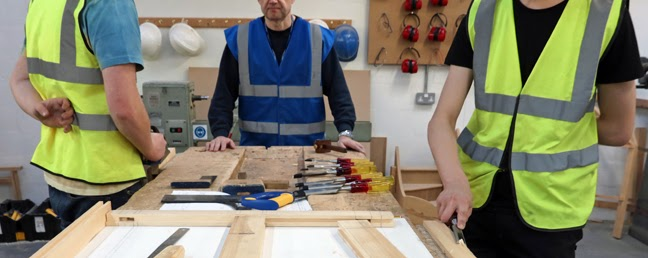 Carpentry students working with one hand behind their backs