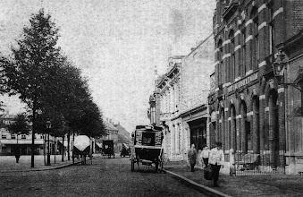 Photo: De zuidzijde van de Heuvel in begin van 1900. Het koetsje op de voorgrond staat voor hotel de Gouden Zwaan, daarmee werden gasten van het hotel naar het station gereden.