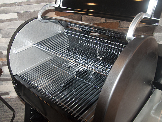 A grill with the lid up showing the cooking grates.