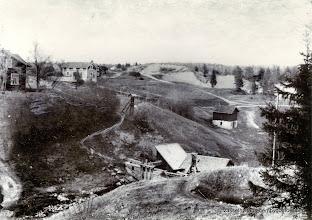 Photo: Dammen, 1910-tal damm och linspel. Vattenhjul som kraftkälla I slutet av 1800-talet innan el- och motordrift var tillgängligt, drevs ett stationärt tröskverk på Dammen med vattenkraft. Vattenhjulet var placerat vid den fördämning av Dammbäcken som fanns kvar efter den nedlagda hyttan. (Wasselhyttan) Vattenhjulet var byggt i trä med en diameter av två meter och en bredd av femtio centimeter. Kraften överfördes till ett linspel via kugghjul (se skiss). Anläggningen var inbyggd i en träbyggnad. (se foto). Linspelet fram till trösklogen var ca 150m långt och vilade på trästolpar med stödhjul (se skiss). Tröskverket var ett hembygge som bestod av en övre del med slagtrumma och skakare varifrån säden föll ned i en rensmaskin i våningen under. Förutom tröskverk drevs även en sk spånhyvel för tillverkande av takspån. Vattenhjulet startades och avstängdes från trösklogen med en längsgående manöverlina.
