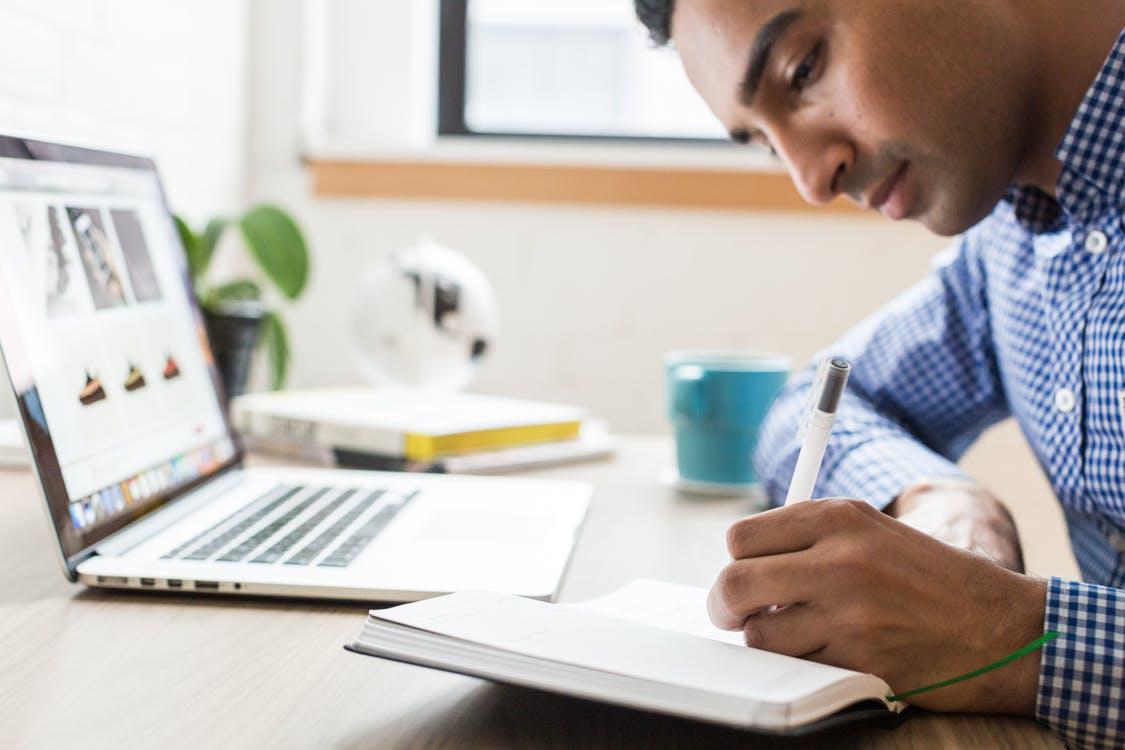 A man writes next to a laptop