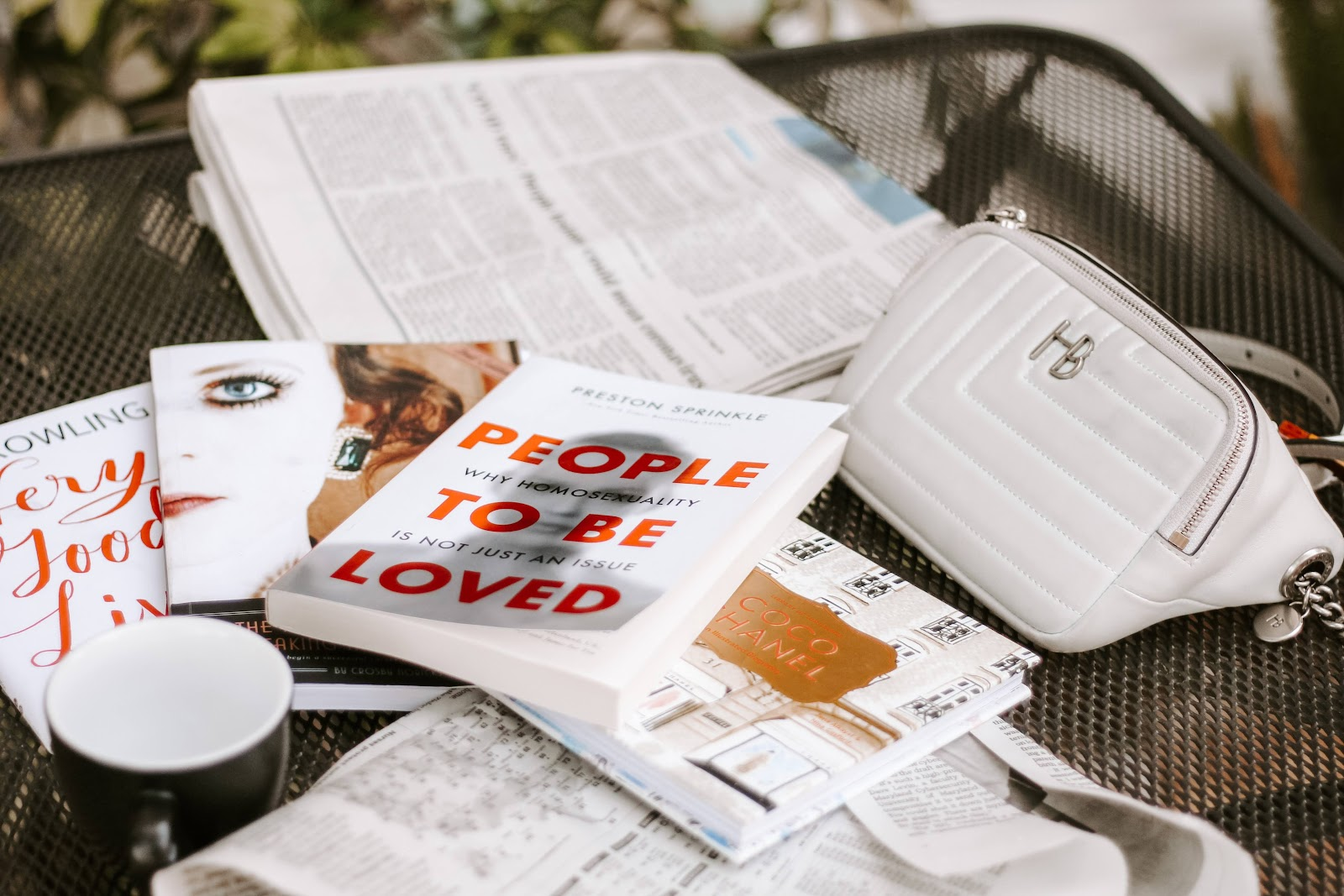 Books and a newspaper on a sidewalk table with Maggie's stylistic fanny pack