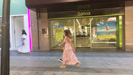 Transeúntes  caminando ayer por el Paseo de Almería junto a la oficina central de Bankia, tras conocerse los contactos con CaixaBank.