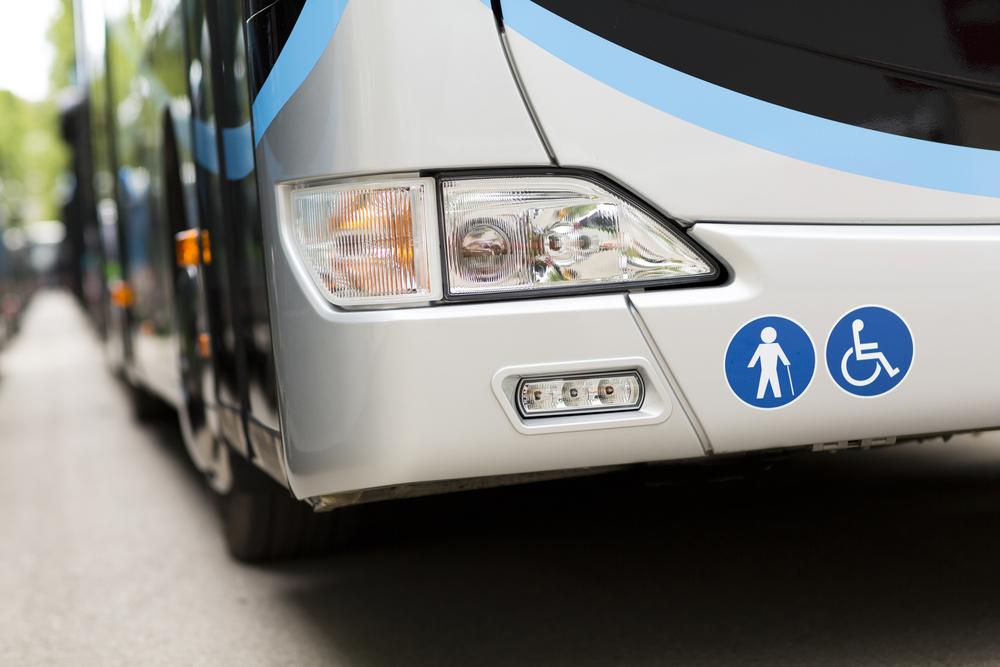 Frente de ônibus com foco no farol e adesivos sinalizando ser apto para idosos e deficientes