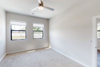 Bedroom with plus carpet, ceiling fan, neutral colored walls, and windows