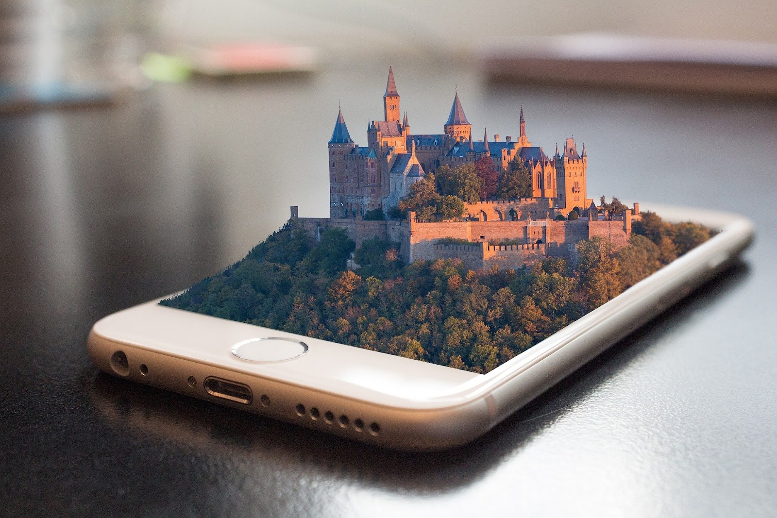 smartphone lying flat on a table with a computer-generated 3D image of a castle rising above the surface