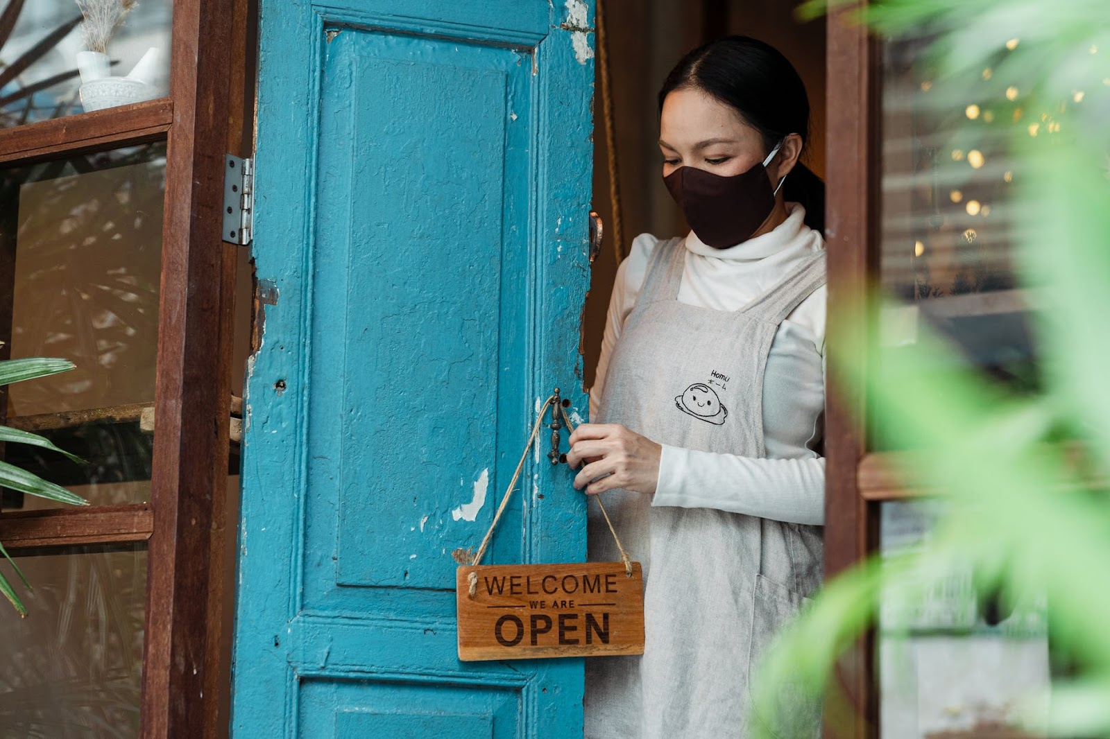 reopen your premises woman at blue door with open sign