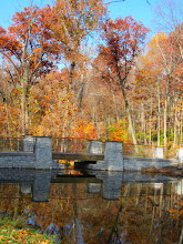 Photo: Autumn foliage and bridge reflected in Dogwood Pond at Hills and Dales Metropark in Dayton, Ohio.