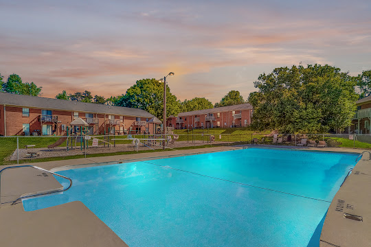 Lindsey Manor's refreshing swimming pool with a children's playground and apartment buildings in the background