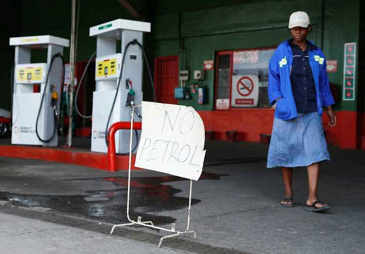 "A woman walks past a ""No Petrol"" sign at a fuel station in Harare, Zimbabwe, October 9, 2018."