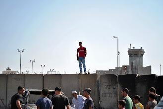 Photo: A Palestinian youth stands above the apartheid wall separating the West Bank from Jerusalem, where the majority of Palestinians are not allowed to enter.