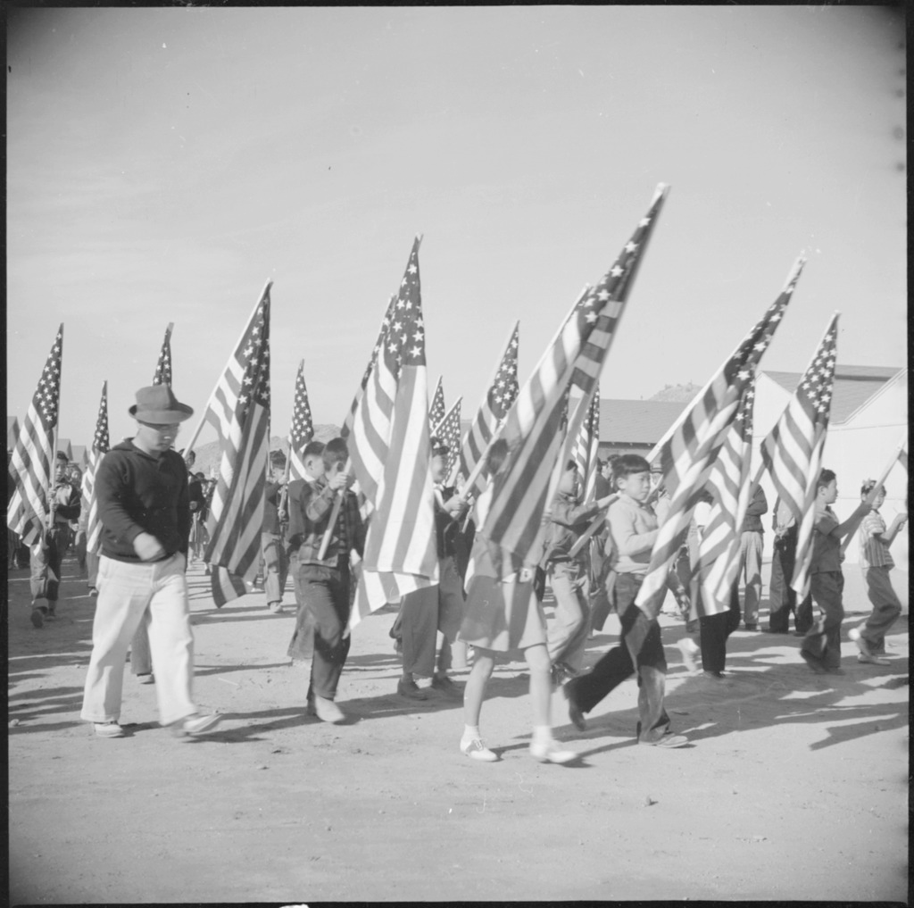 Japanese American school children marching in a harvest festival parade at Gila River concentration camp. They are carrying large American flags.