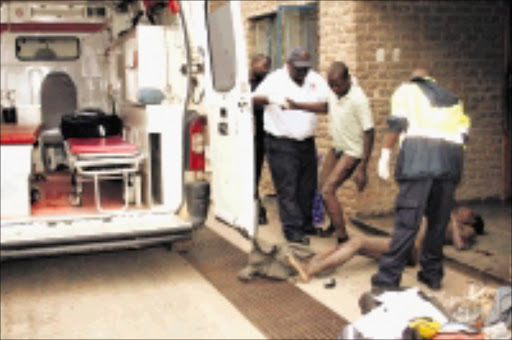 too late : Promise Mathumbu is helped into an ambulance by a paramedic while his friend, Thabo Silaule, lies dead on the ground. The two were assaulted by residents of Mhala after they were alllegedly caught stealing. Pic.ANDREW HLONGWANE. 08/11/2009. © Sowetan.