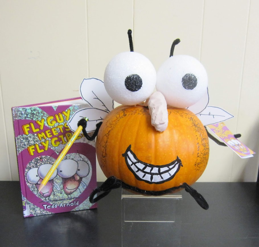 Pumpkin decorated like book character The Fly Guy with eyes, wings, and legs attached.