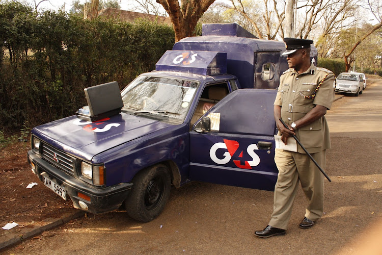 A police officer walks by a G4S car branded that was abandoned at Upperhill during a past incident.