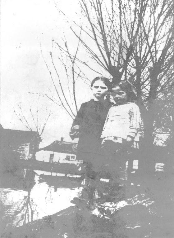 """Zdjęcie: Zdjęcie wykonane około 1934 roku wChrobrzu na Podzamczu. Po lewej stronie widać drewniany budynek """"rzeźni"""", za którym płynęła Nida. Na zdjęciu pierwsza zprawej Izabela Dobaj obok Celina Dobaj (fot. zarch. Izabeli Rogóż zd. Dobaj)."""
