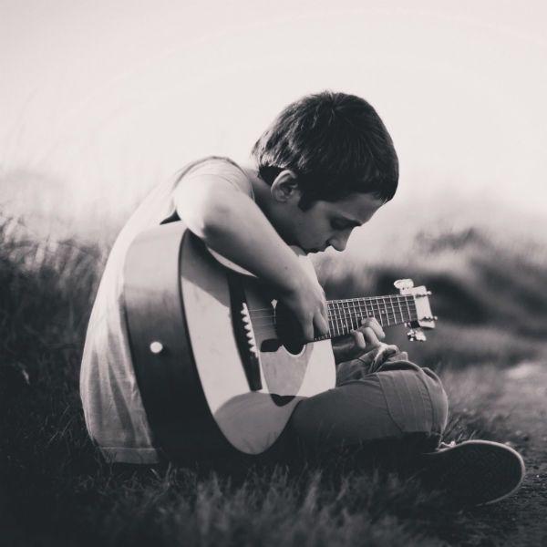 Niño tocando la guitarra de nylon sentado en la grama