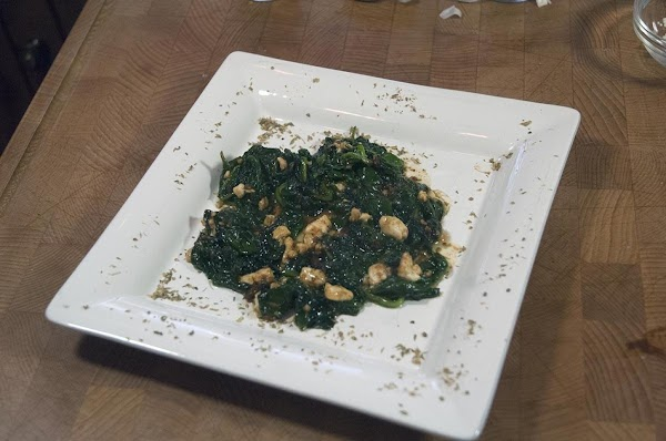 Divide the spinach between two serving plates.