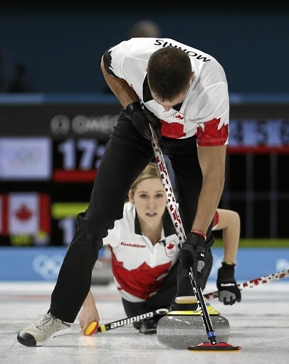 Clean sweep: Canada's Kaitlyn Lawes watches as John Morris works up a sweat as he sweeps during the opening round of the curling event at the Winter Olympics. Picture: REUTERS