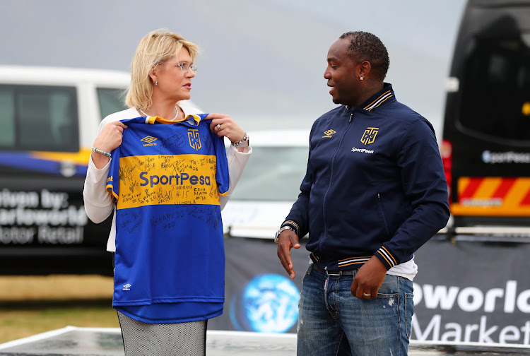 Cape Town City FC head coach Benni McCarthy hands a jersey to Sharlene van Dijk, Dealer Principle Barloworld during the club's Barloworld VW Sponsorship announcement at Bungalow, Clifton, Cape Town on 2 November 2017.