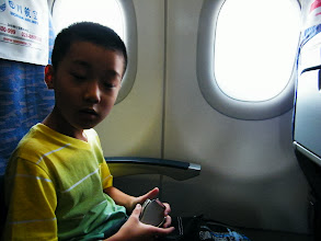 Photo: journey hometown in summer 2013 shakes doubts and plows hope: here warrenzh 朱楚甲 just settled in the plane before launch. he likes to use his fonepad to kill time.