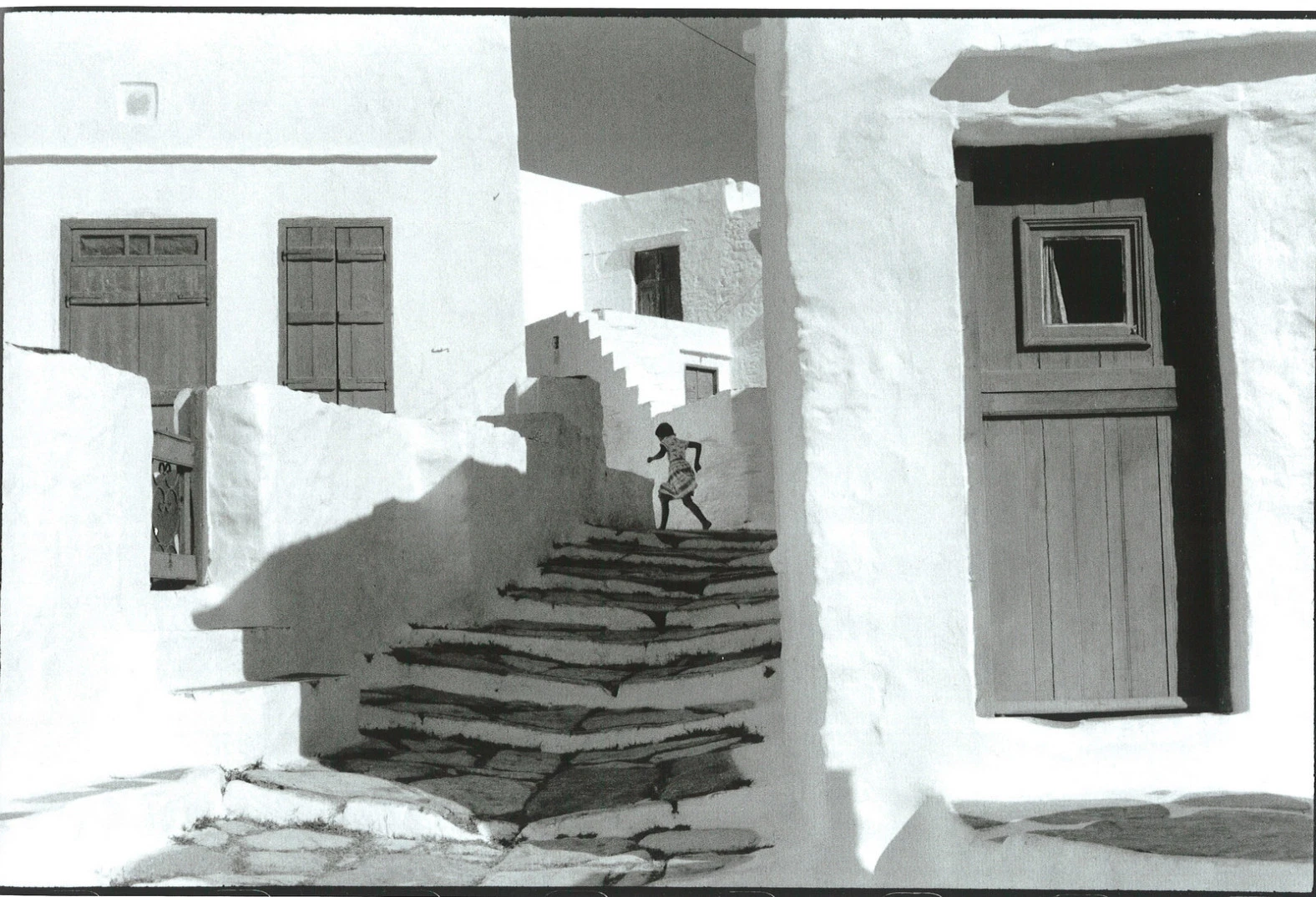 A black and white image of a child running up a staircase in a white village, by famous photographer Henri Cartier-Bresson