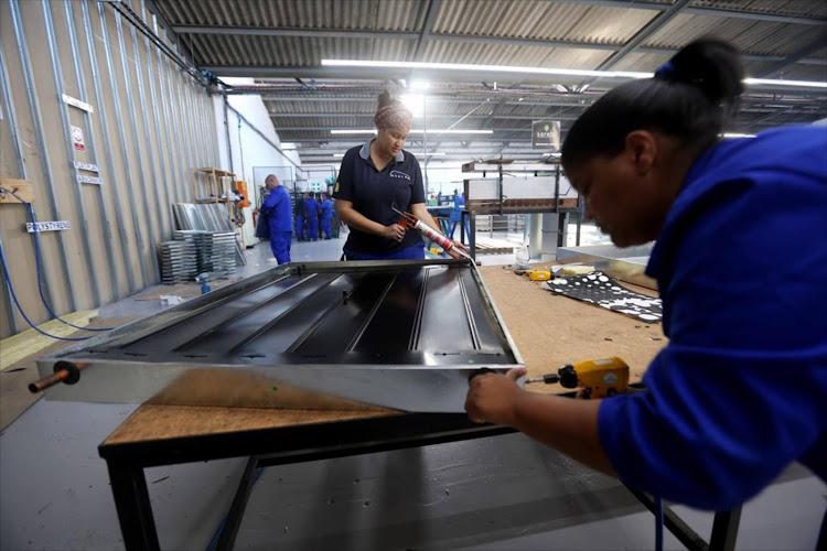 Workers in Atlantis, north of Cape Town, assemble solar panels in a factory that also produces LED lights. Manufacturing, the economy's fourth-biggest sector, is expected to have contributed positively to GDP in the second quarter.