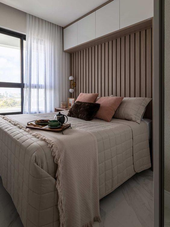 Quarto de casal com revestimento de madeira no local da cabeceira, armário superior e piso marmorizado.