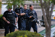 Heavily-armed Dallas Police Department officers investigate a 'credible threat' at the department's headquarters in Dallas, Texas, USA, 09 July 2016. Five officers died and seven were injured after an ambush assault by a gunman during a protest rally in Dallas on 07 July.  EPA/ERIK S. LESSER