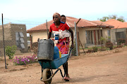 Paseyesi Xihlangu from Risinga village in Giyani travels 1.5km  from her house to fetch water carrying  her baby.