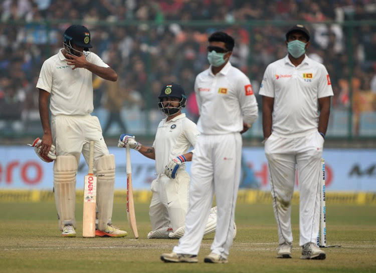 Sri Lanka cricket players wear masks in an attempt to protect themselves from air pollution as Indian captain Virat Kohli (2L) and teammate R. Ashwin look on during the second day of the third Test cricket match between India and Sri Lanka at the Feroz Shah Kotla Cricket Stadium in New Delhi on December 3, 2017. Many of Sri Lanka's fielders wore pollution masks to counter a thick smog as play was briefly halted on day two of the third Test against India in New Delhi on December 3.