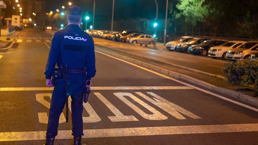 Un agente de la Policía Nacional, en labores de vigilancia en Sevilla durante el toque de queda.