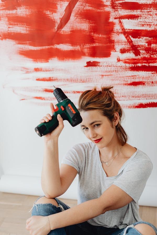 Uma mulher sentada no chão de casa segurando uma furadeira na mão