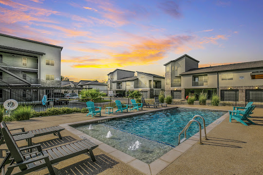 Tinsley Place's swimming pool with gray lounge chairs and teal adirondack chairs surrounding at dusk