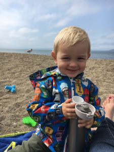 Toddler boy smiling at the beach