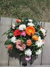 Photo: couronne printanière, composition piquée fleurs utilisées: gerberas( grosse marguerite), roses, oeillets blanc feuillages : laurier et autres  prix environ 30 euros  selon les fleurs utilisées