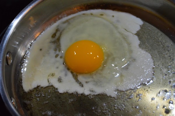 Break egg into skillet closer to the edge farther from you. Immediately prick white...