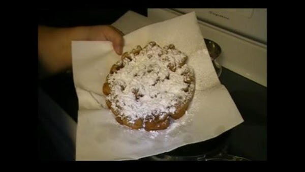 Sift powdered sugar on top as soon as you remove it from the oil....