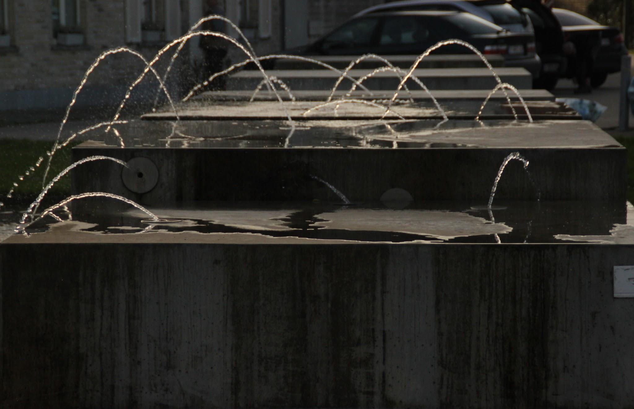 Photo: Vanuit de wanden van de betonnen blokken verschijnen subtiele fonteinstralen.