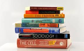 Stack of college textbooks, ranging from Cellular Biology and Sociology to a Latin textbook