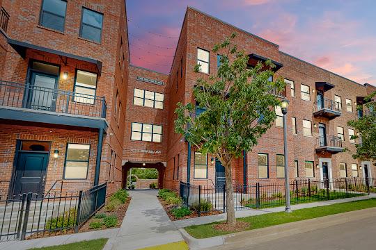 The Village Flats brick apartment building at dusk