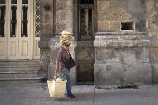 Cuba-Havana-hatman.jpg - A vendor walks down a street in Havana.