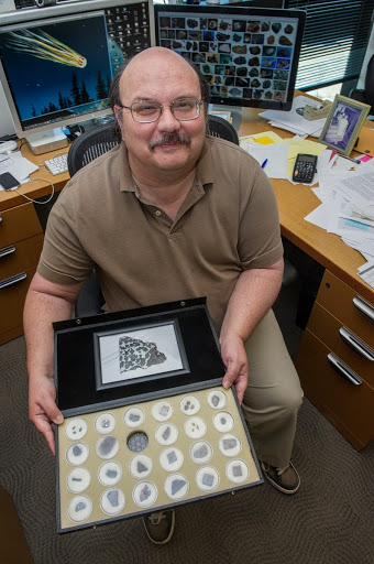 LEAD OF THE METEROID ENVIRONMENT OFFICE AT MARSHALL SHOWS VARIOUS METEORITES IN HIS COLLECTION.
