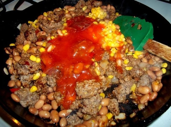 Now, add seasonings, beans, corn, taco sauce and 1/2 cup of dressing. Reduce heat...