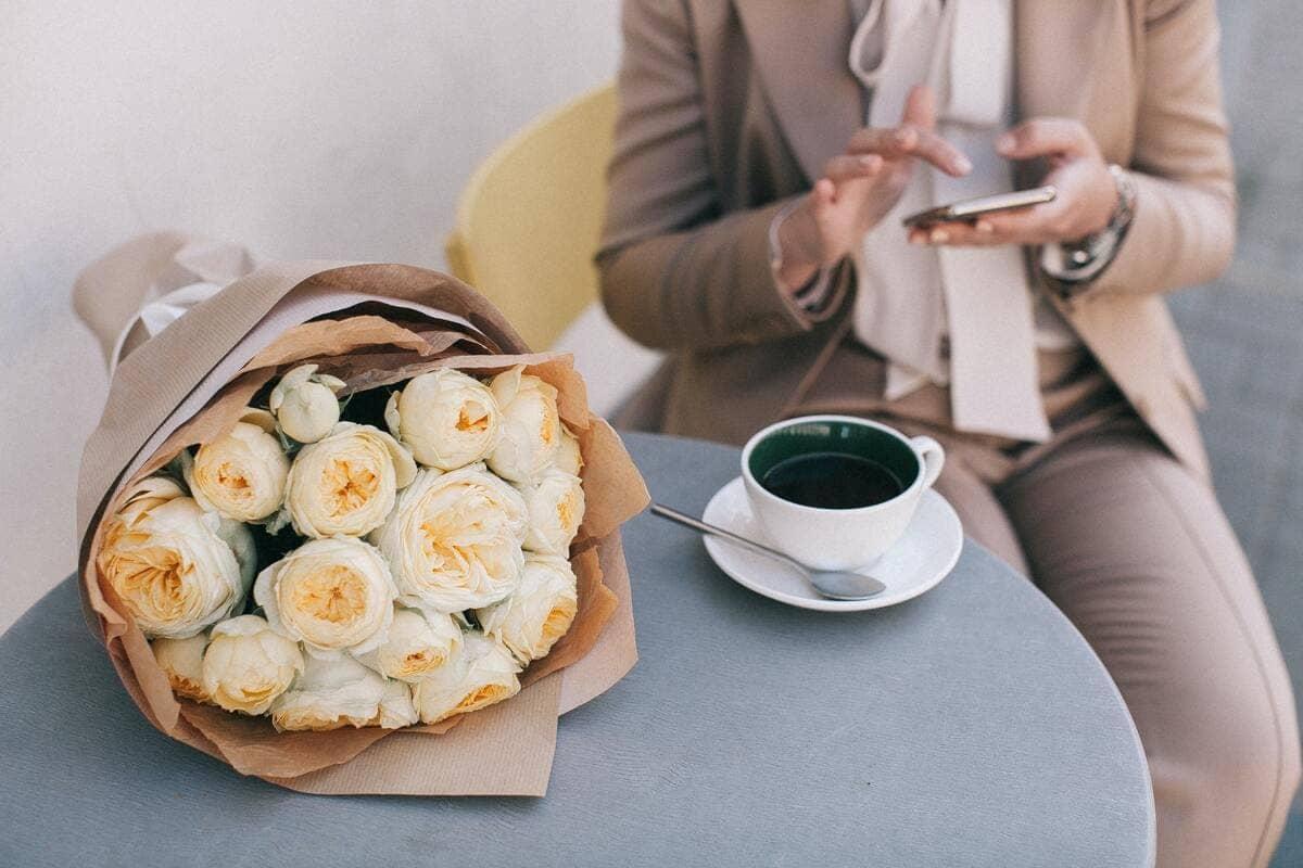 Un mazzo di fiori gialli posto su un tavolino con accanto una tazza di caffè