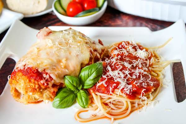 Stuffed Chicken Parmesan On A Plate With Spaghetti.